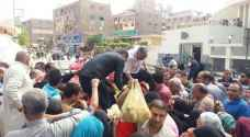 Hundreds of Egyptians wait their turn for a bite of potatoes