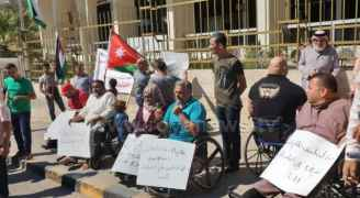 People with disabilities protest in front of Finance ....