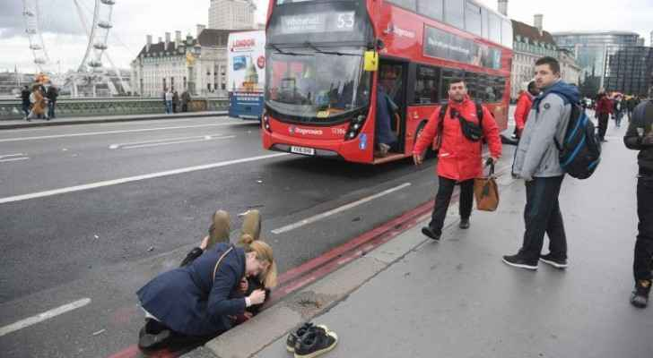 A woman assists an injured person on Westminster Bridge in London after Saturday's terrorist attack.