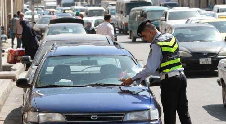 A policeman places a parking ticket on the windshield of a driver in Jordan.
