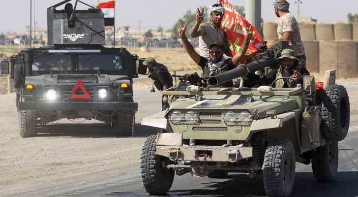 Iraqi forces flash victory signs as they advance toward Kirkuk. (NPR)