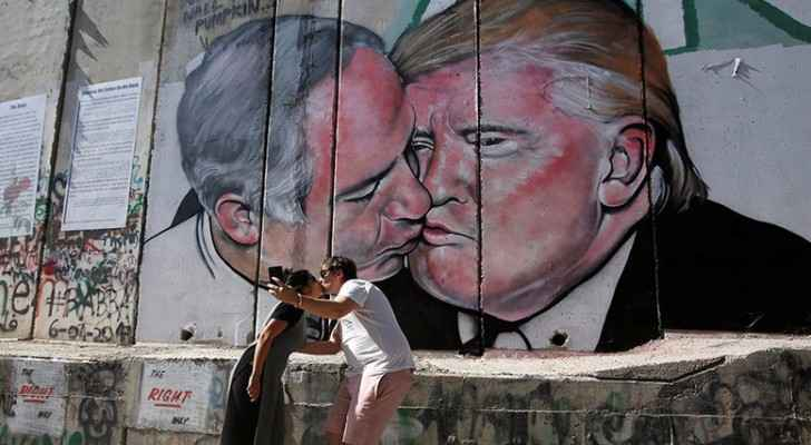Tourists have their picture taken with the Trump-Netanyahu mural. (Reuters)