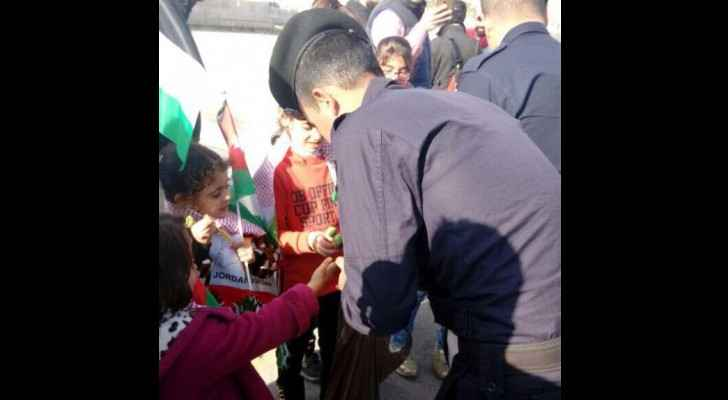 A policeman hands out candy to orphans in Amman. (Roya)