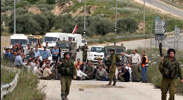 Palestinians in the village of Ras Karkar and foreign activists blocking a road in protest in Ramallah, 2007 (Getty Images)