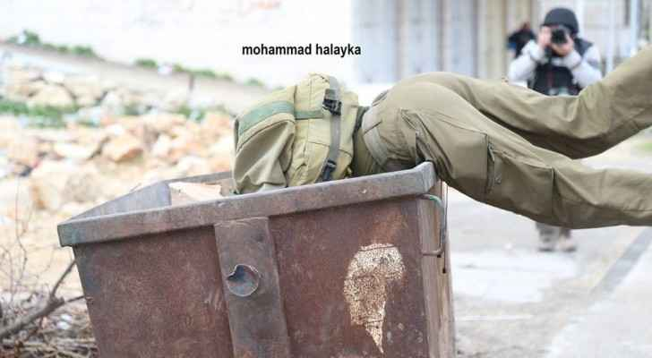 It is unknown how or why the Israeli soldier fell into the trash container. (Mohammad Halayka)