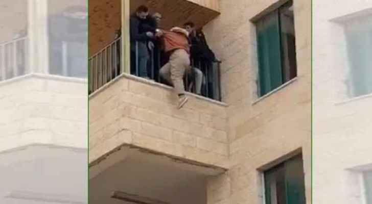 Guards and students pulling the girl who tried to jump off the building