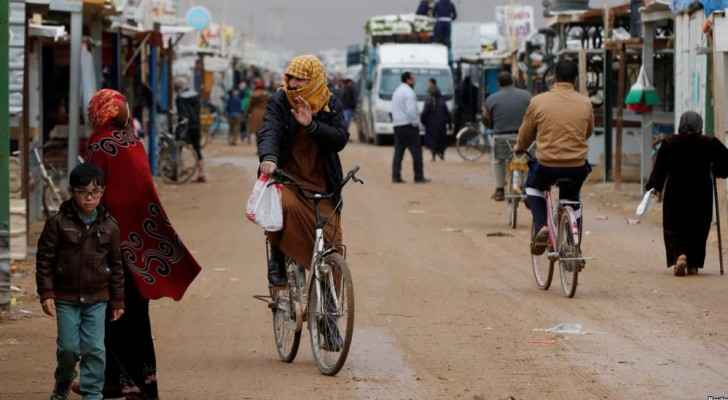 Syrian refugees ride bicycles during rainy weather at the Zaatari refugee camp in the Jordanian city of Mafraq. (VOA News)