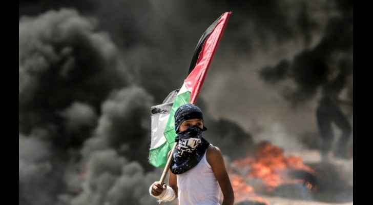A Palestinian boy holds his national flag during clashes between protesters and Israeli forces near the Gaza border on May 14, 2018. (AFP / MAHMUD HAM