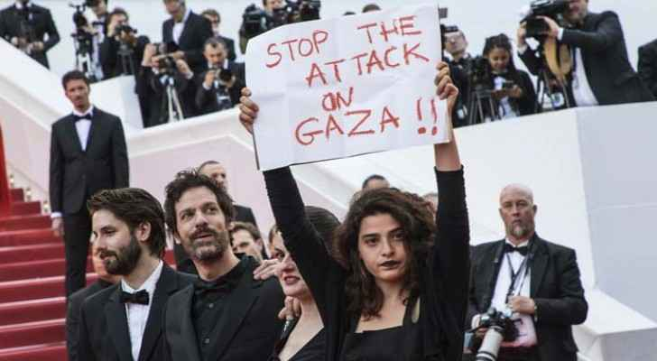 "Lebanese actress Manal Issa holds a sign reading ""Stop the Attack on Gaza"" as she walks the famous red carpet in Cannes. (AP)"