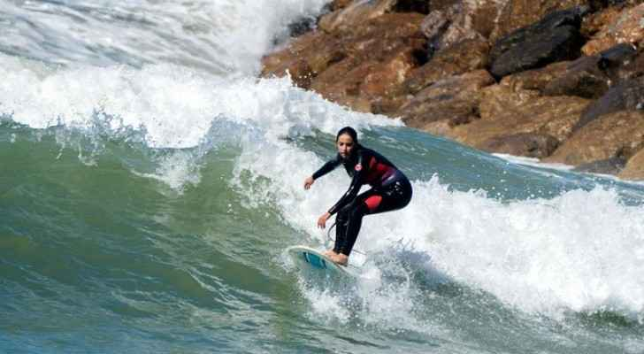 Meriem, a 29-year-old Moroccan engineer and surfer, surfs off the coast of Rabat on April 1, 2018. (AFP)