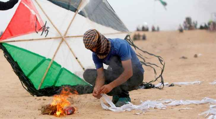 Palestinian rioter prepares incendiary kite on Gaza border (AFP)
