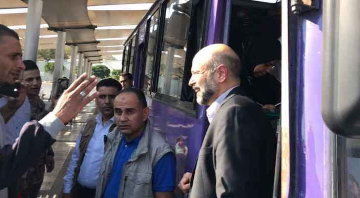 Razzaz rides a bus in Tabarbour during his surprise visit. (Roya)
