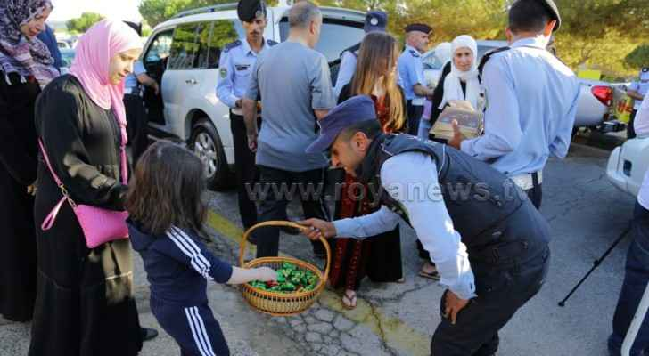 A police officer hands out candy to a little girl in Amman on Eid Al Adha. (Roya)