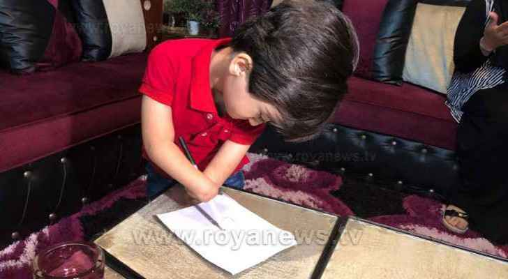 Ruwaid writes on a piece of paper during his interview with Roya. (Roya)