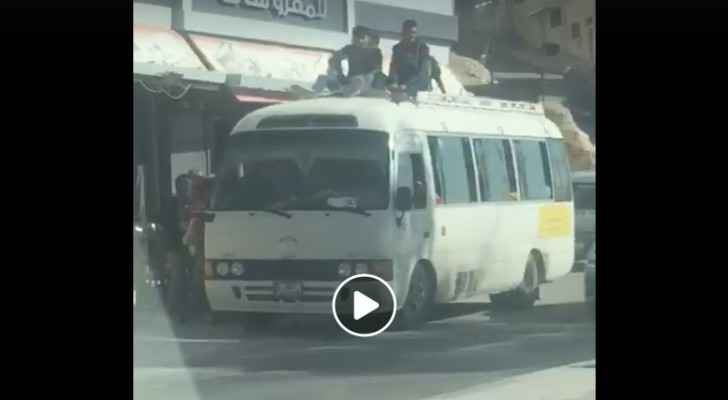 Students sit on top of a public transport bus in Zarqa. (Roya)