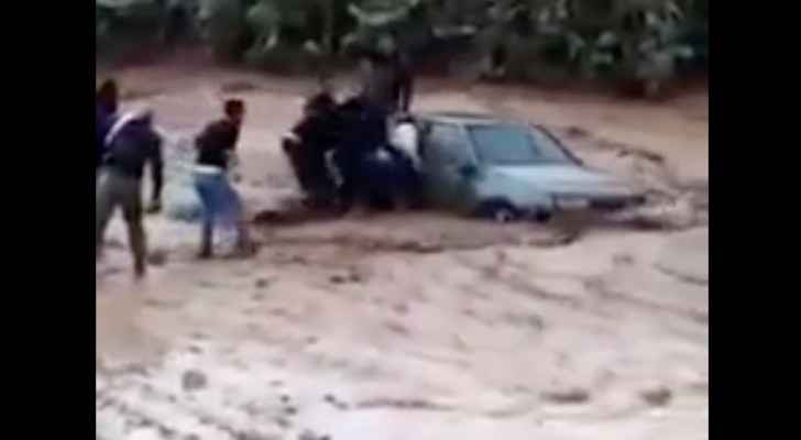Rescue teams save passengers in a car that was swept away by floods in Madaba on Friday, November 9, 2018. (Roya)